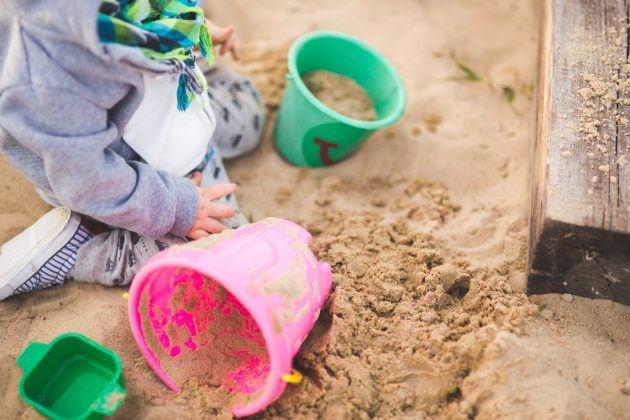 child plays in sand