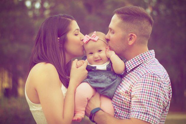Mor og far kysser baby