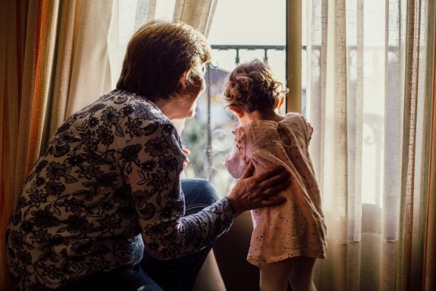 grandmother and grandchild looking out of window