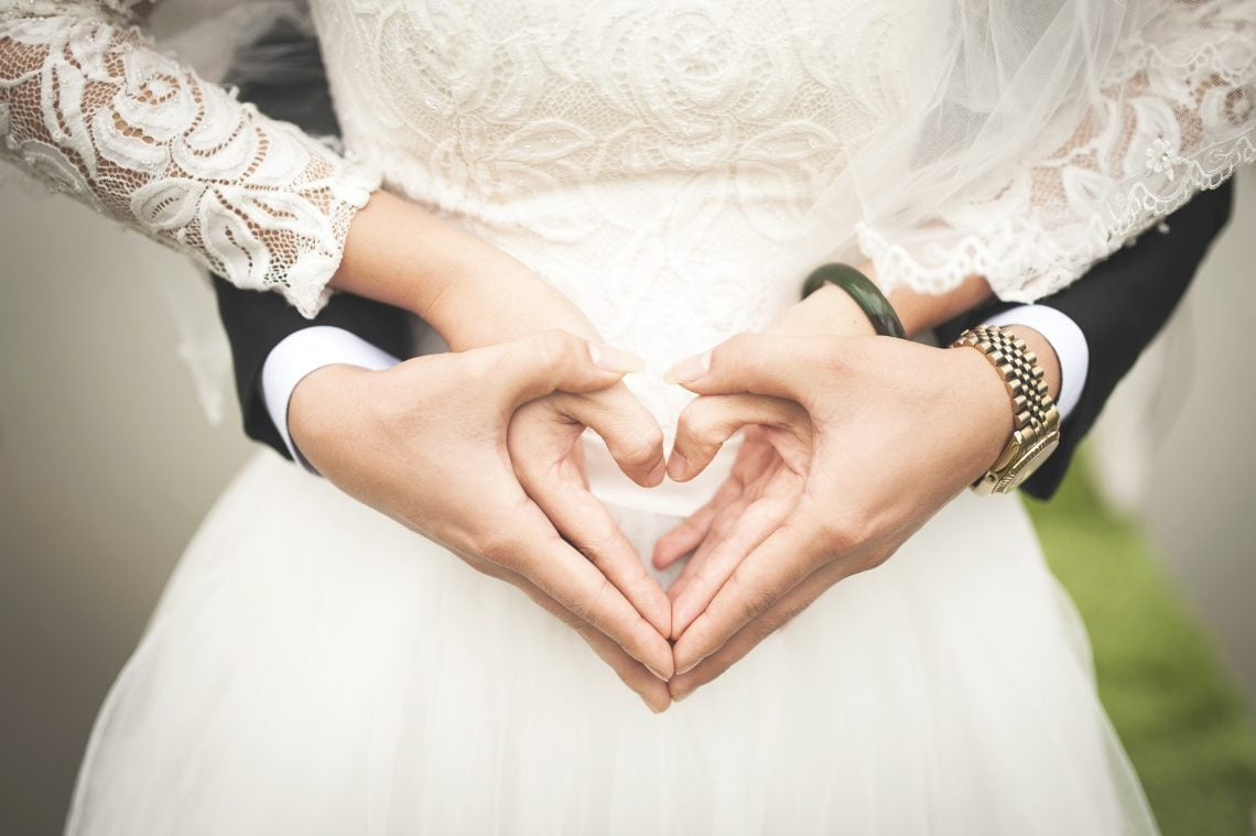 Bride and groom holding hands as a heart