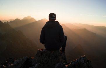 mand sidder på et bjerg til solnedgangen