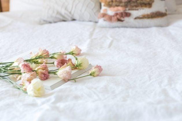seng hvorpå der ligger lyse roser