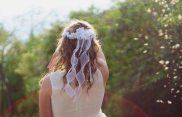 ung pige i hvid kjole med krøllet hår