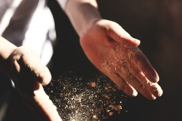 Hænder med støv eller mel imellem