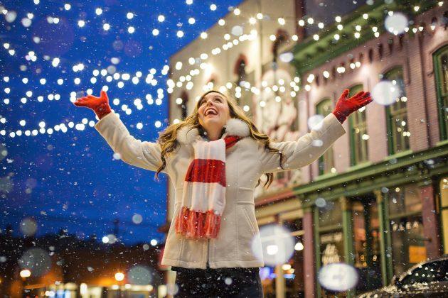 Glad kvinde foran julelys