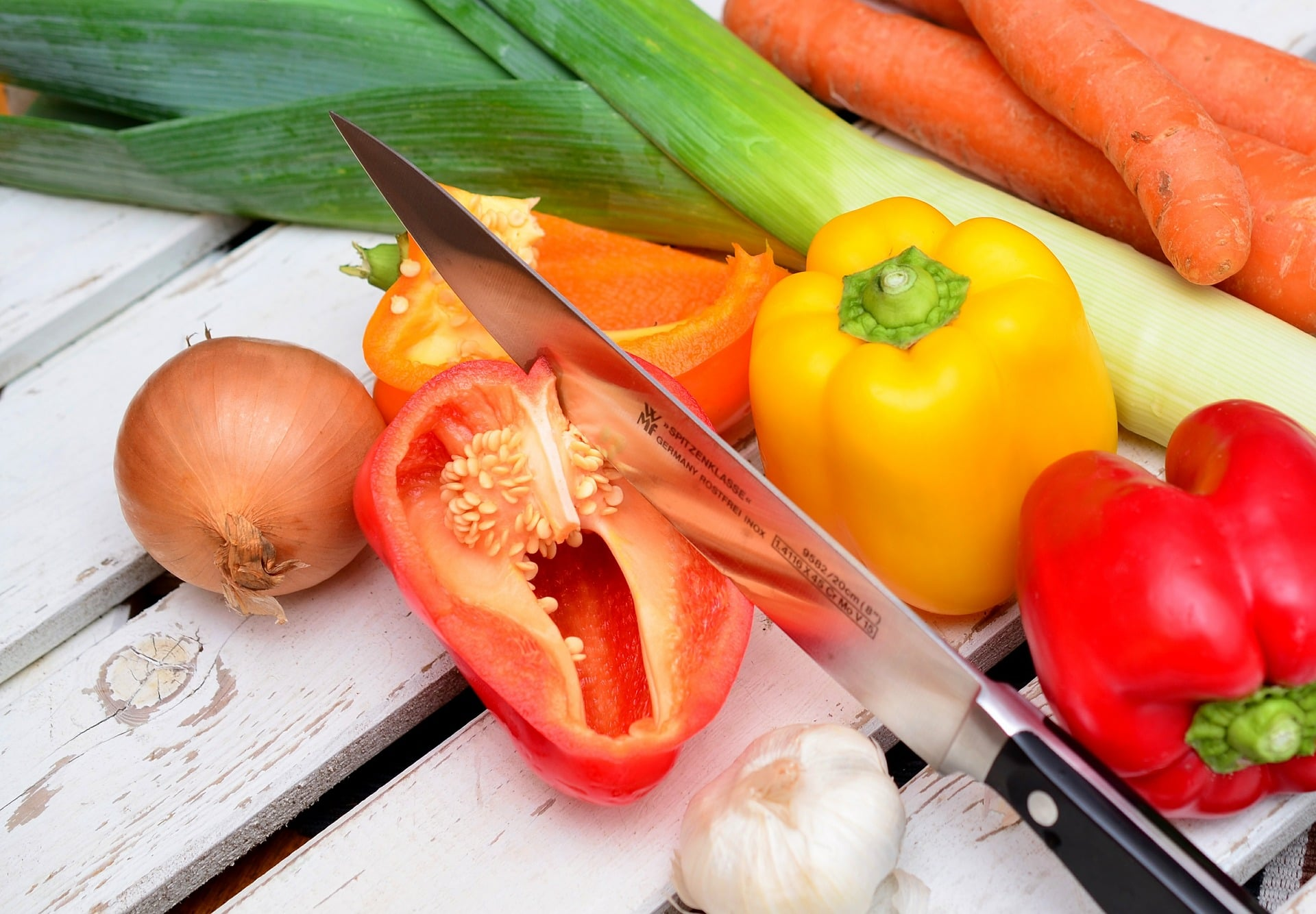 Grøntsager, løg, peberfrugter og en køkkenkniv