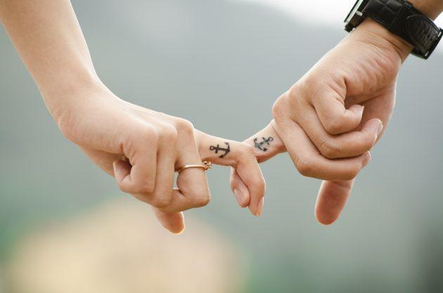 To hænder med tattoo på fingeren holder hinanden i pegefinger
