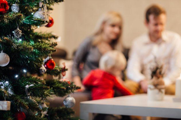 Juletræ med familie på 3 personer i baggrunden