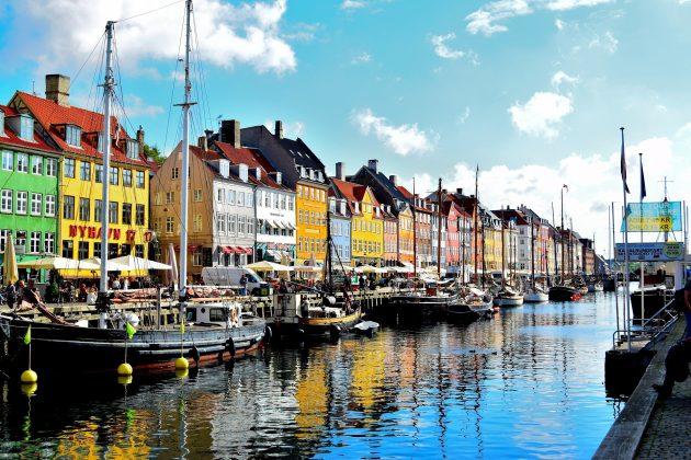 Farverige huse på række i Nyhavn og både foran
