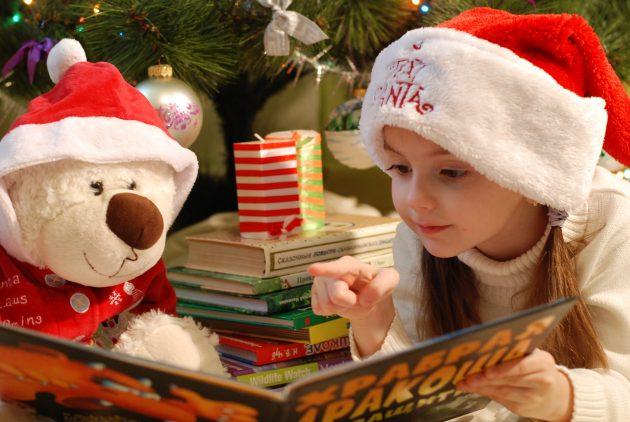 Pige med nissehue og bamse med nissehue kigger i bog