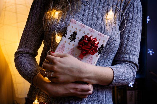 Kvinde i grå striktrøje holder en gave og har julelys om sig