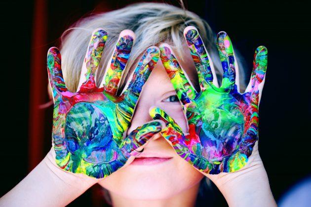 Lille barn der holder hænderne op foran hovedet med farverig maling på hænderne