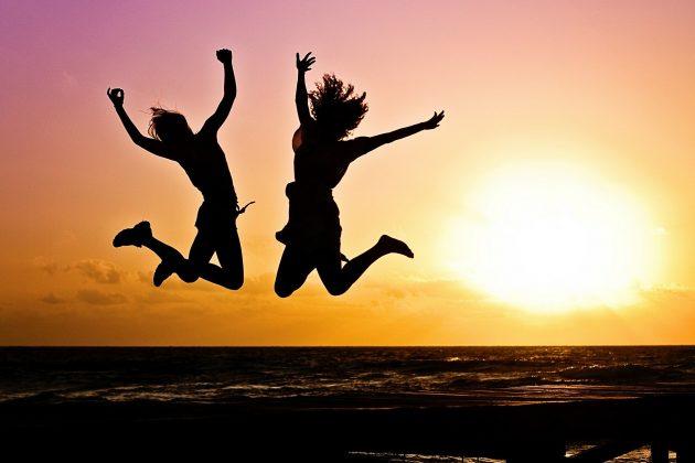 To piger der hopper i solnedgangen med havet i baggrunden