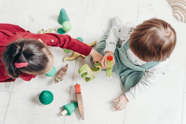To børn der sidder og leger med legetøj set oppefra