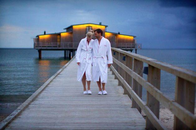 Mand og kvinde går på badebro i solnedgang