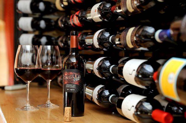 Vinflasker i rækker og to glas vin