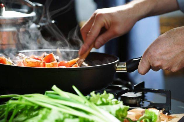 Person steger grøntsager på en pande