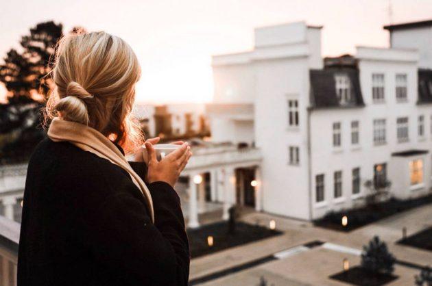 Kvinde står med en kop kaffe i hånden og kigger ud over et hotel