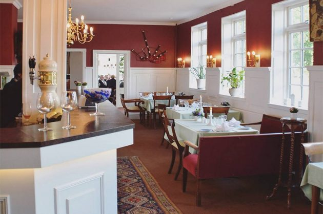 Restaurant i en kro med opdækkede borde og bar