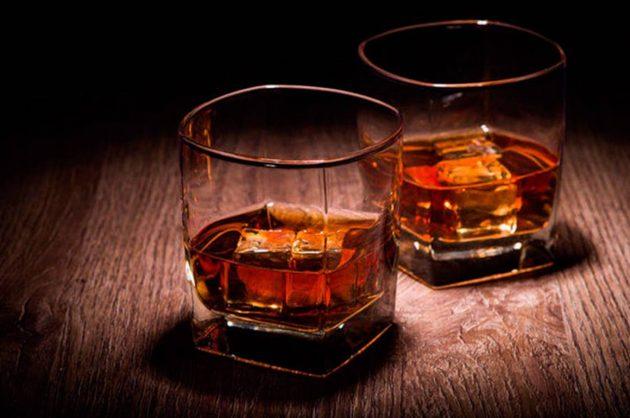 To glas med rom i på træbord