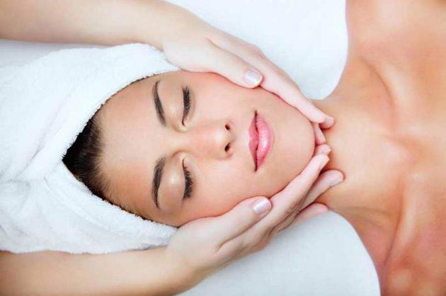 Kvinde får ansigtsbehandling med håndklæde om håret