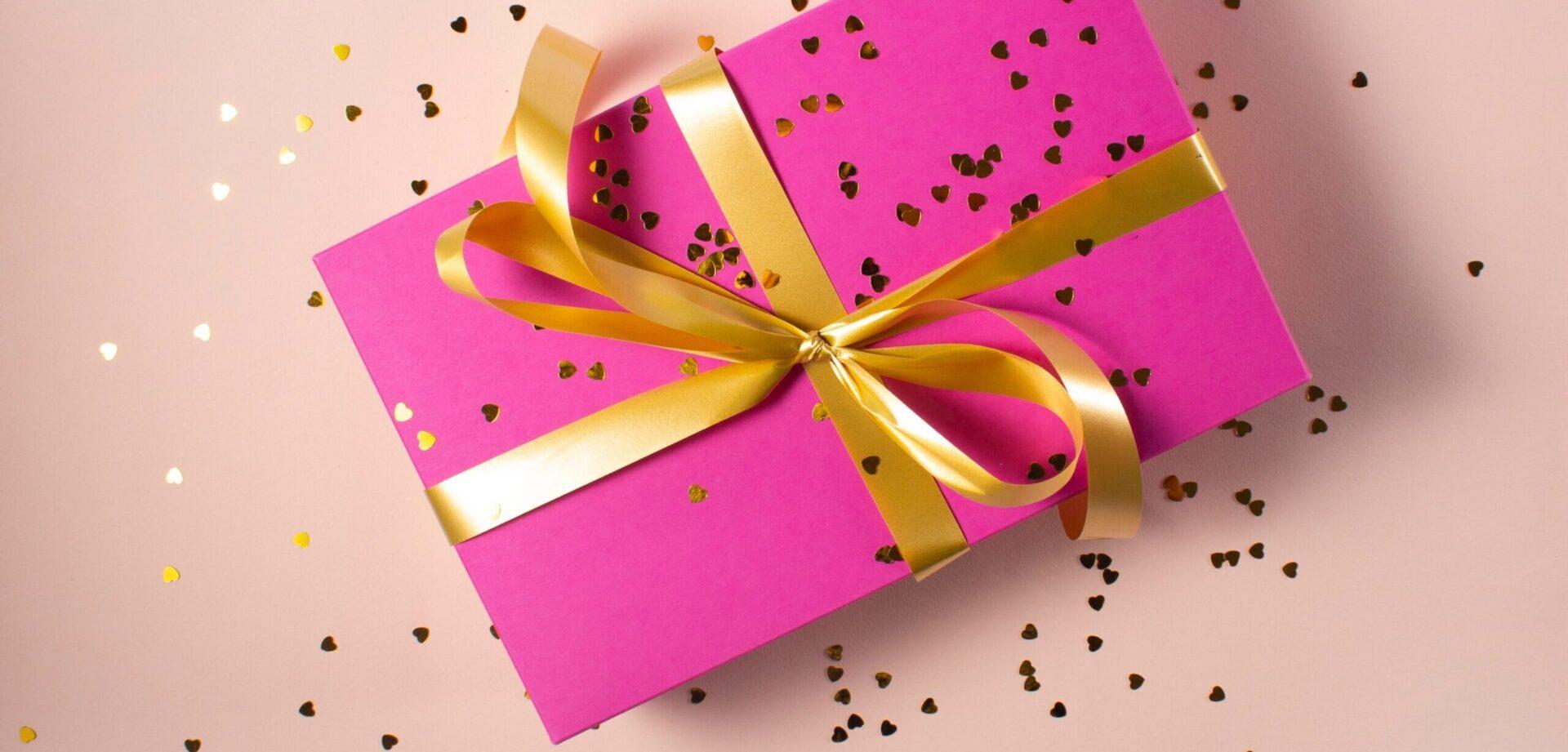 lyserød gave med guld bånd